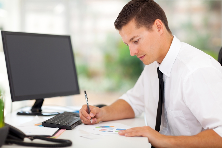 man working on forms at computer